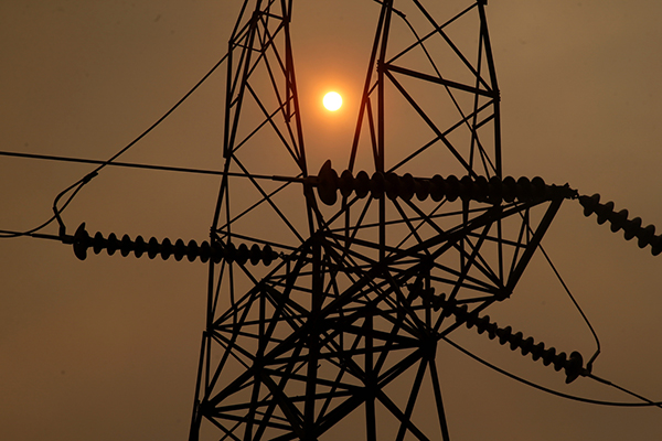 The sun peaks through the smokey skies from the Camp Fire and a PG&E transmission line November 12, 2018, three miles west of Pulga, Calif. Photo by Karl Mondon, Bay Area News Group