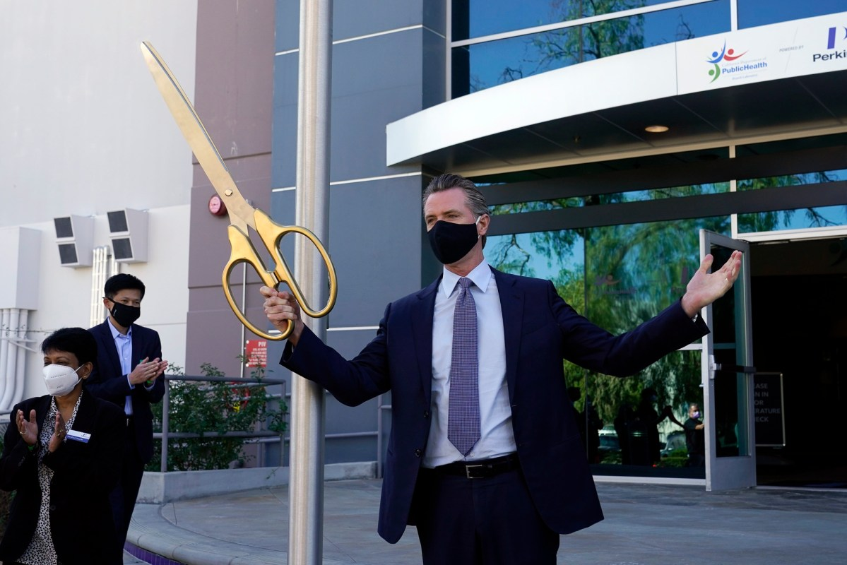 Gov. Gavin Newsom participates in a ribbon cutting ceremony at a new $120 million, 134,000 sq. foot coronavirus testing facility Oct. 30, 2020, in Valencia. The state is working with corporate partner PerkinElmer to run the lab which will enable the state to process an additional 150,000 COVID-19 tests per day. Photo by Marcio Jose Sanchez, AP Photo/Pool
