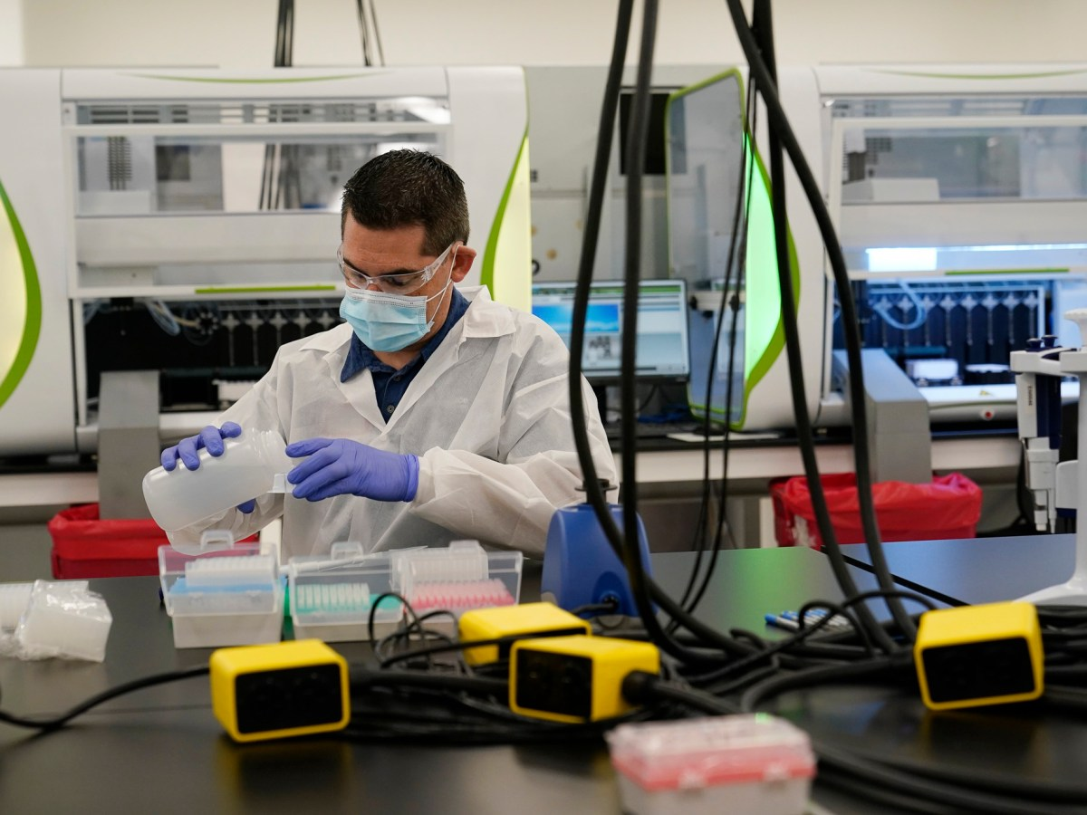A technician conducts COVID-19 tests at a new facility Friday in Valencia on Oct. 30, 2020. The lab, run by PerkinElmer, was expected to allow the state to process an additional 150,000 COVID-19 tests per day but so far result times have lagged. Photo by Marcio Jose Sanchez, AP Photo/Pool