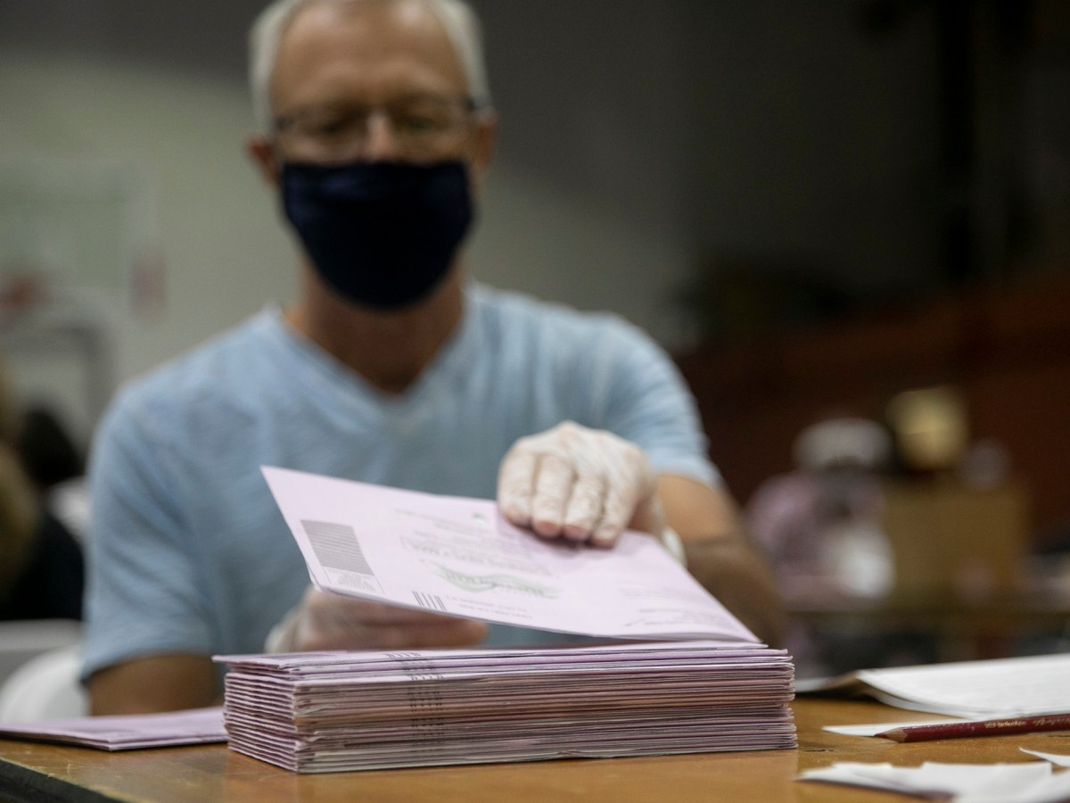 San Ramon resident Geoffrey Hillier volunteers extracting ballots in Martinez on Oct. 31, 2020. Photo by Anne Wernikoff for CalMatters