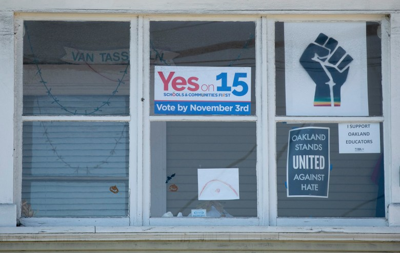 Signs supporting Prop 15 and Oakland Schools hang in the window of a home in Oakland on Oct. 31, 2020. Photo by Anne Wernikoff for CalMatters