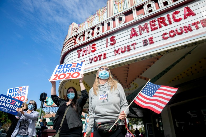 A small crowd carrying signs and flags gathered at the Grand Lake Theatre on Nov. 7, 2020. Photo by Anne Wernikoff for CalMatters
