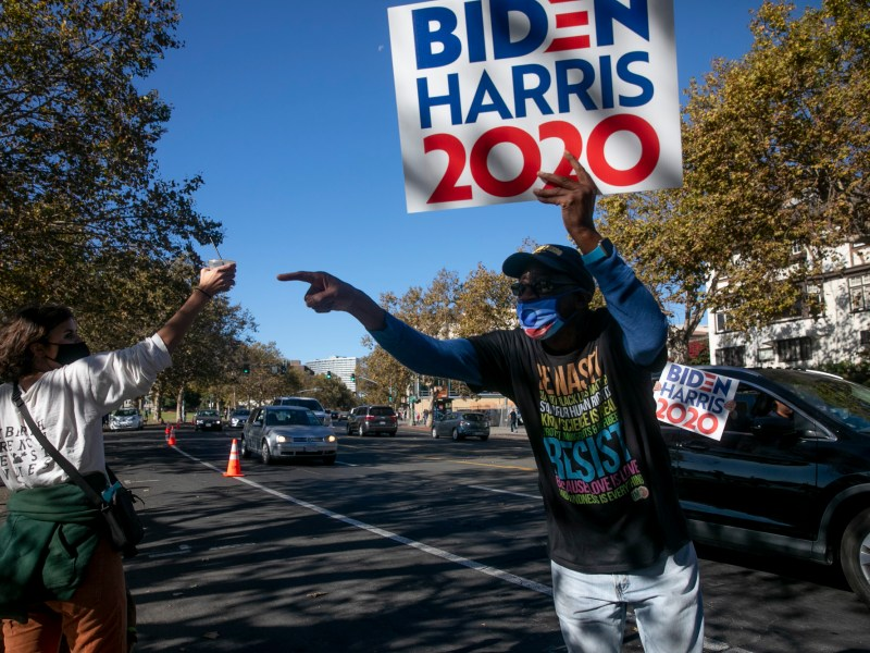 """She's from Oakland!"" shouts Jackson Taylor, 69, as he carries a Biden-Harris sign along Grand Ave near Oakland's Lake Merritt on Nov. 7, 2020. Photo by Anne Wernikoff for CalMatters"