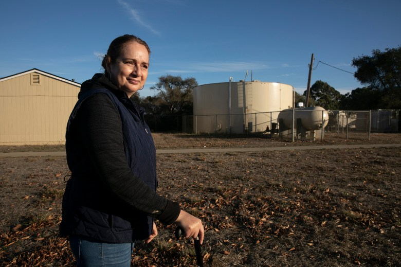 Aracel Fernández stands near the water tank that serves the migrant worker community where she lives near Watsonville on Nov. 10, 2020. Fernandez says her family and many others in the compound depend on bottled water for drinking and cooking due to a strong smell and taste of chlorine in the tap water. Photo by Anne Wernikoff for CalMatters