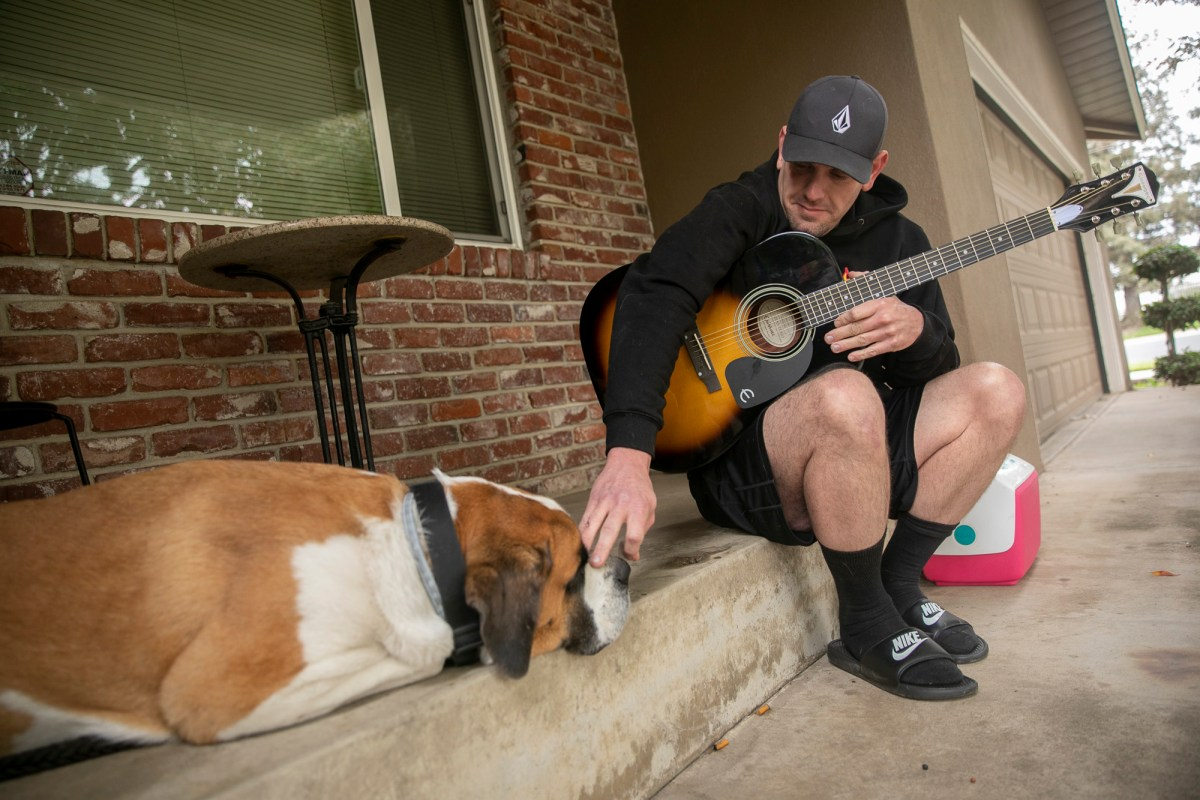 Matt Hoffman pets his Saint Bernard Jackson while on hold with Bank of America at his girlfriend's house in Escalon on Nov. 13, 2020. Hoffman, who has been unemployed since suffering a stroke last year, has been unable to access his benefits since July. Photo by Anne Wernikoff for CalMatters