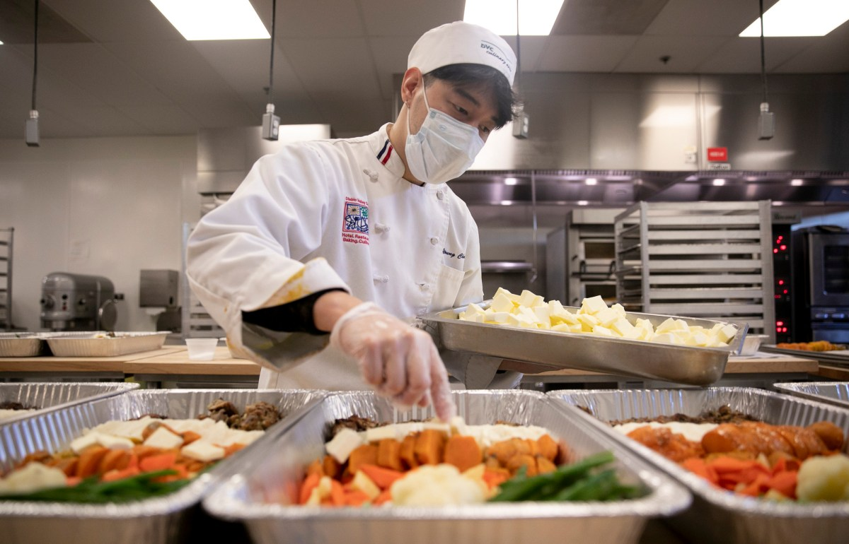 Advanced cuisine student Soon Gi Hwang places butter pats into trays of prepared thanksgiving dinners which will be frozen and distributed through the campus food pantry at Diablo Valley College on Nov. 18, 2020. According to Hwang, the culinary program has provided meals for 800 food insecure families since the beginning of the semester when the program began serving the campus food pantry en lieu of the restaurant and food counter which are closed due to the pandemic. Photo by Anne Wernikoff for CalMatters