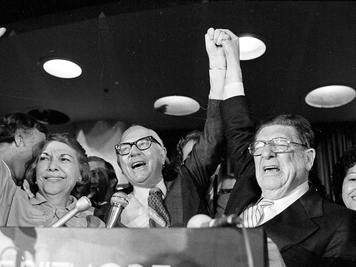 Paul Gann, left, and Howard Jarvis hold up their hands as their co-authored initiative Propsition 13 takes a commanding lead in the California primary, in Los Angeles, June 7, 1978. Photo by AP Photo