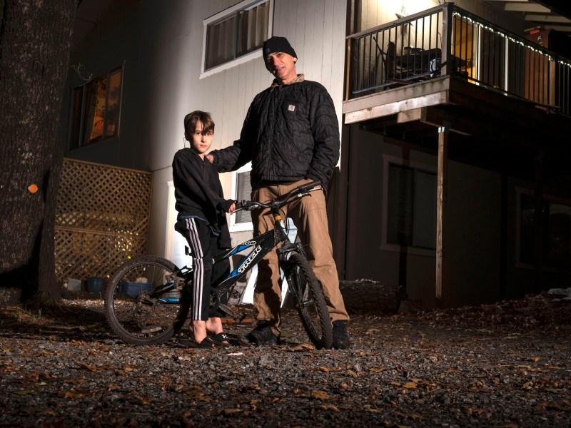 Jacques Gene en su casa de Cool, cerca de Sacramento, con su hijo Wyatt de 7 años. Se encuentran entre los cientos de miles de californianos que se están preparando para que termine la ayuda pandémica, a medida que expiren los beneficios federales por desempleo y el estado levante su moratoria de desalojo. Foto de Hector Amezcua para CalMatters