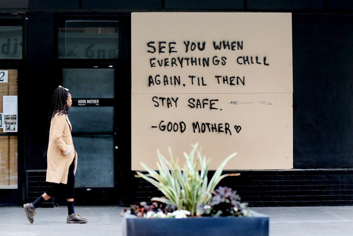 A pedestrian walks past boarded up windows of a business on 13th Street in Oakland during the first shelter-in-place order on March 24, 2020. Photo by Ray Chavez, Bay Area News Group