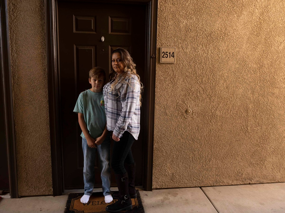 Teresa Trabucco and her son are photographed in front of the door of their home.