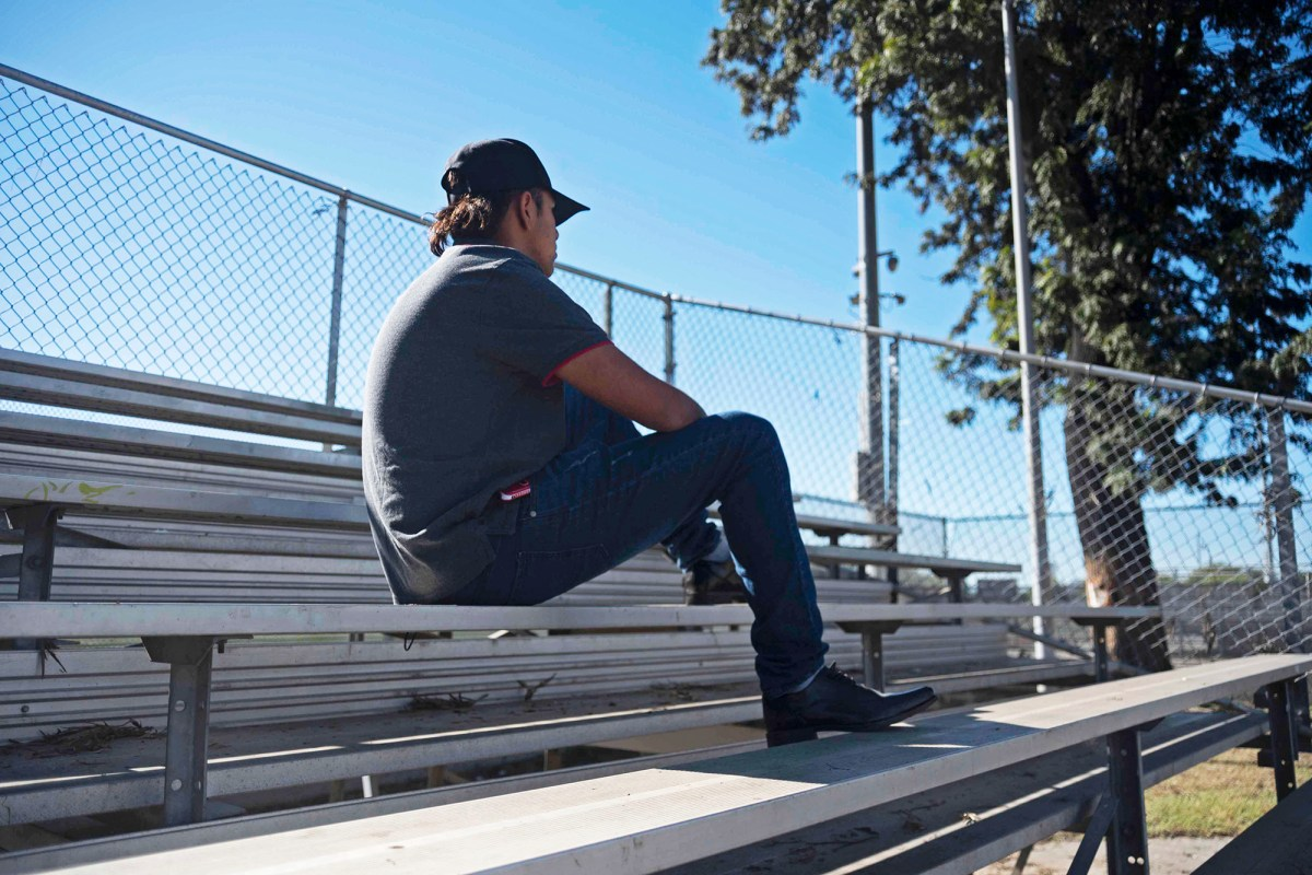C.A.T.S student Isaac Portillo sits in South Central LA's Bethune Park on Nov. 29, 2020. Photo by Tash Kimmell for CalMatters.