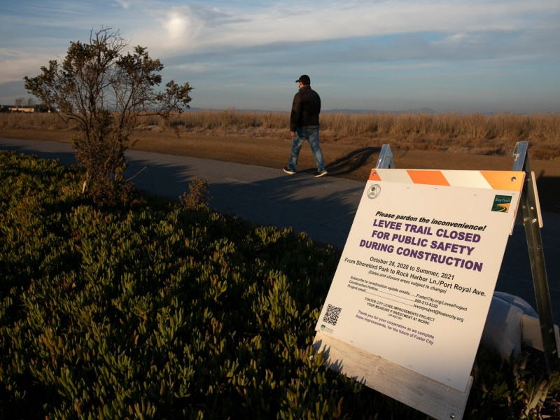 A man walks along a pathway closed due to levee construction in Foster City on Dec. 2, 2020. In 2018, Foster City passed a bond measure to fund levee repair in order to maintain FEMA accreditation and protect from future flooding and sea level rise. Photo by Anne Wernikoff for CalMatters