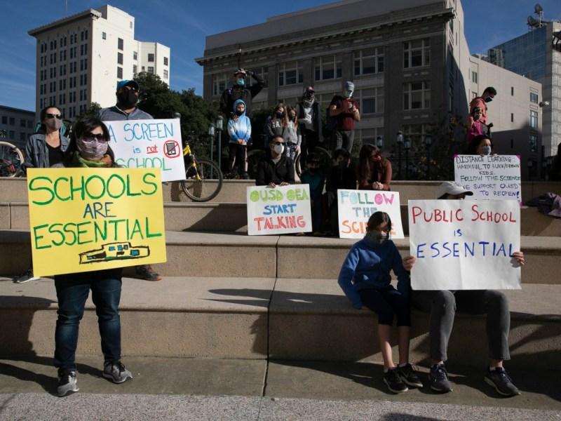 Las familias se reunieron en Frank Ogawa Plaza en Oakland para protestar por la continuación del cierre de escuelas públicas en California el 5 de diciembre de 2020. Foto de Anne Wernikoff para CalMatters