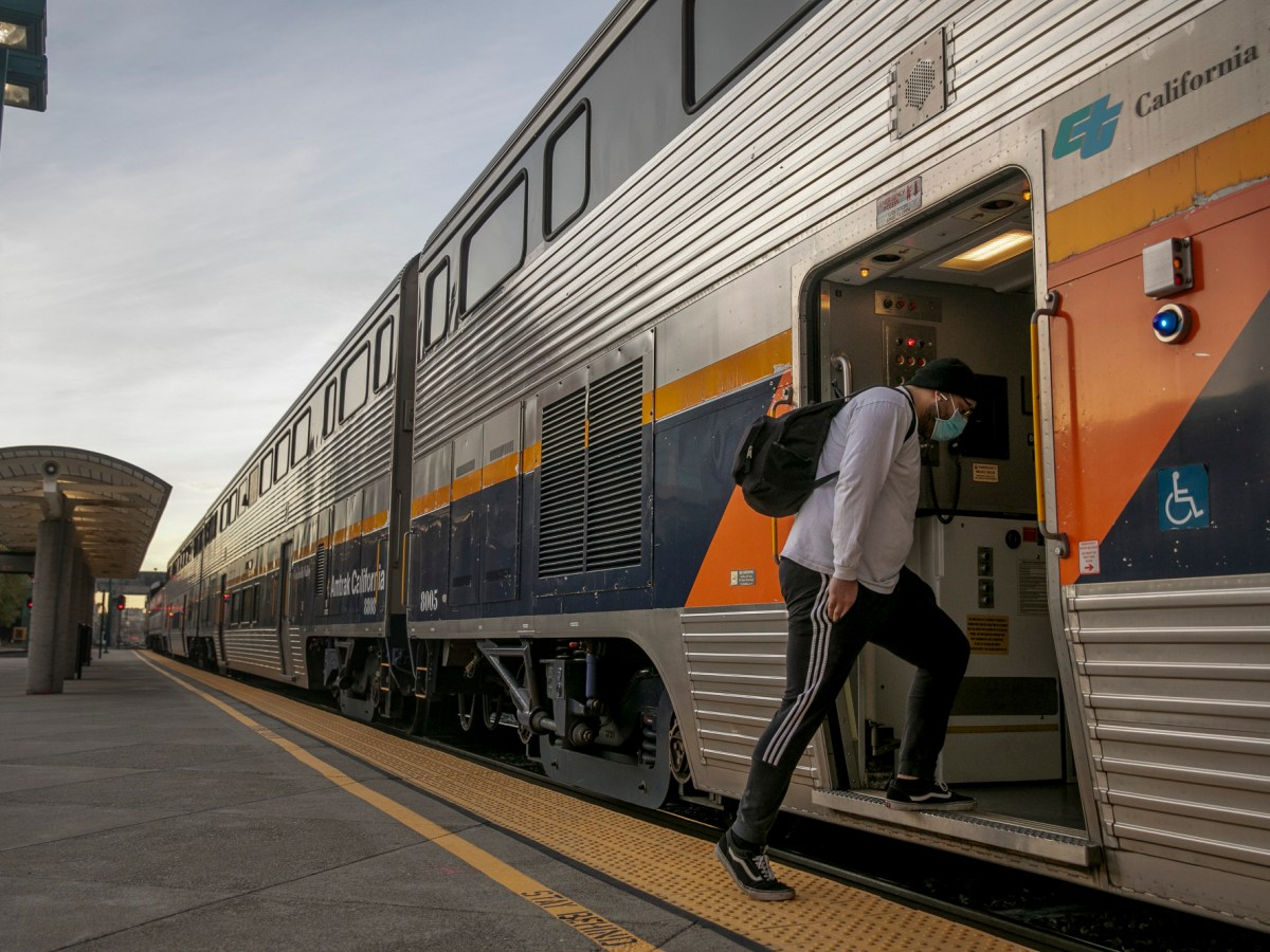 A passenger boards a Bakersfield-bound train at the Emeryville Amtrak station on Dec. 16, 2020. Photo by Anne Wernikoff for CalMatters
