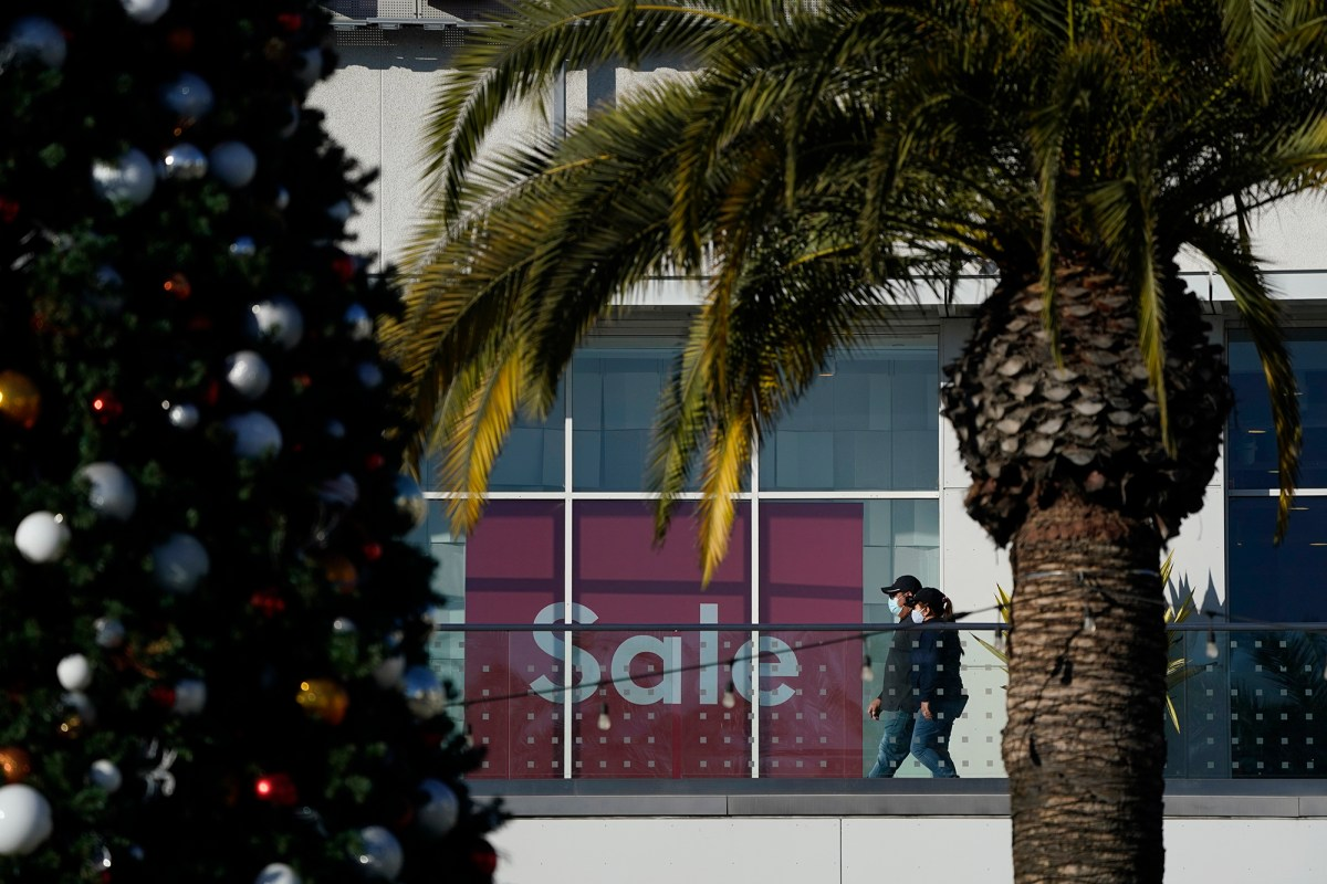 Shoppers wearing face masks walk past a sale sign and a Christmas tree at The Pike Outlets in Long Beach. Photo by Ashley Landis/AP
