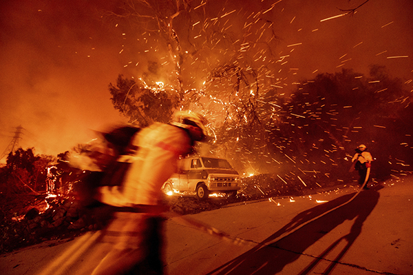 Firefighters battling the Bond Fire haul a hose while working to save a home in the Silverado community in Orange County on Dec. 3, 2020. Photo by Noah Berger, AP Photo