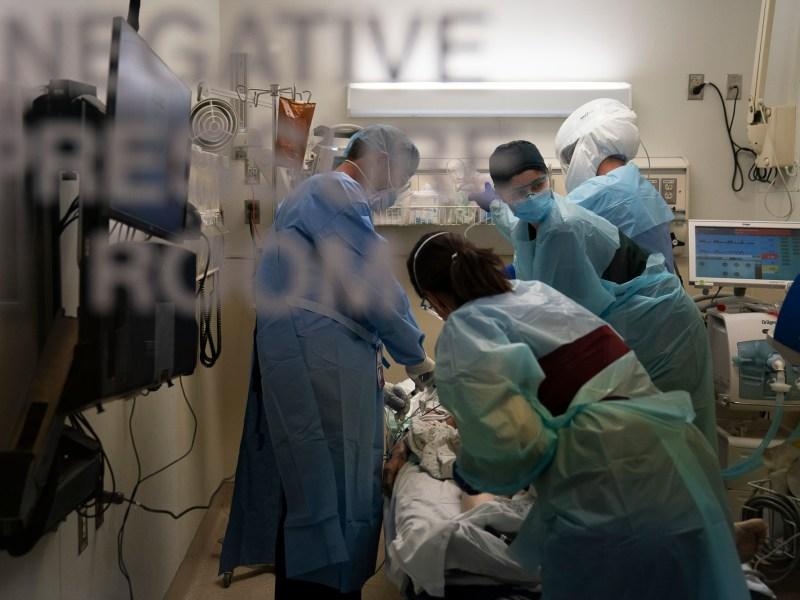 EMT Giselle Dorgalli, segunda desde la derecha, mira un monitor mientras realiza una compresión torácica en un paciente que dio positivo por coronavirus en la sala de emergencias del Providence Holy Cross Medical Center en la sección Mission Hills de Los Ángeles el 19 de noviembre de 2020. Foto por Jae C. Hong, AP Photo