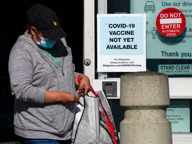 A customer walks past a sign indicating that a COVID-19 vaccine is not yet available at Walgreens on Dec. 2, 2020, in Long Beach. Photo by Ashley Landis, AP Photo