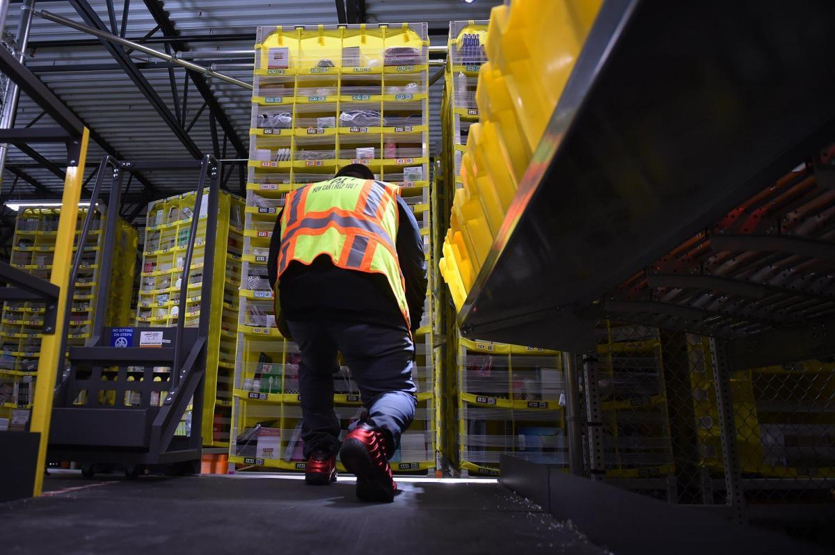 El asistente de proceso de Amazon, Christian Ramirez-Gallegos, se arrodilla mientras clasifica los paquetes en el centro logístico de Amazon al sur de Fresno. Foto de Eric Paul Zamora, The Fresno Bee