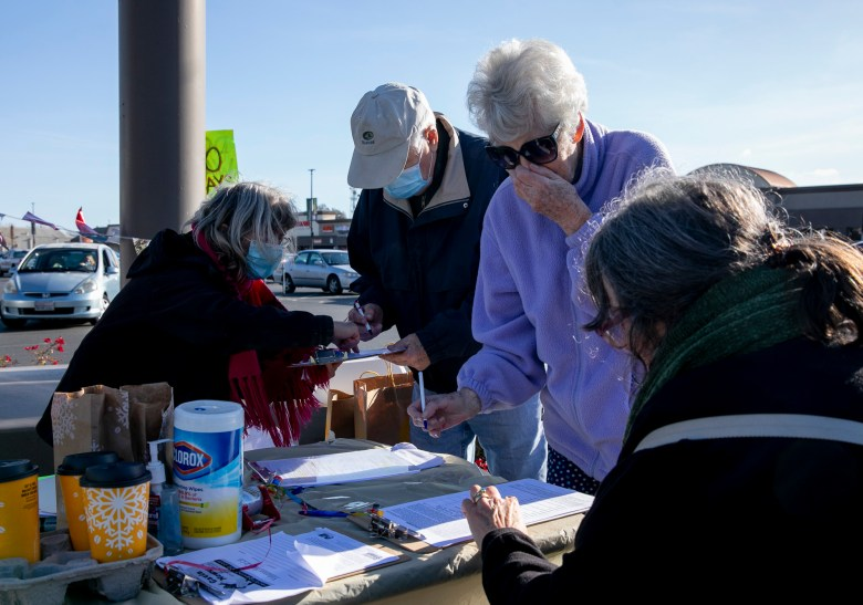 Recall Newsom volunteers help Richard McDougal, left, and his wife, Florence Lauzob, sign the forms during a petition signing event at SaveMart in Sacramento on Jan. 5, 2021. Photo by Anne Wernikoff, CalMatters