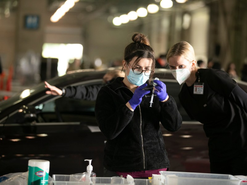 Katherine Ambrose, RN and medical reserve corps member, looks on as Army medic Jenny Rafailov, left, fills a syringe at the COVID vaccination site at Cal Expo in Sacramento on Jan. 21, 2021. Photo by Anne Wernikoff, CalMatters