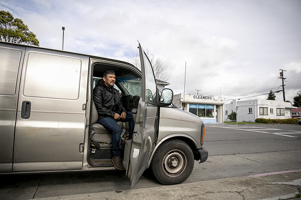 Guillermo Hernandez sits in his van in Richmond on Jan. 28, 2021. Hernandez, who uses his van for his businesses buying and selling second hand goods, lost work after having his license suspended in 2013 for failure to pay a ticket. Photo by Anne Wernikoff, CalMatters