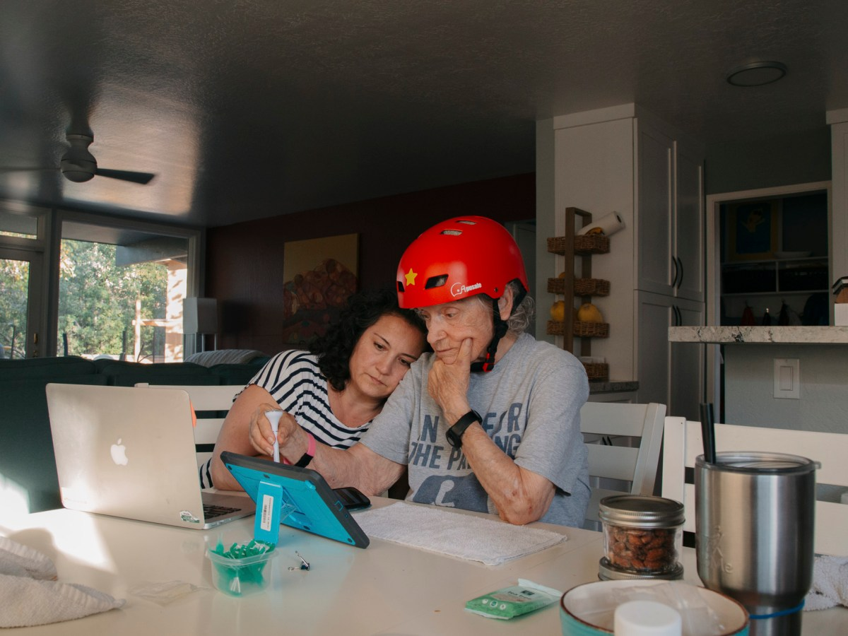 Ann Lucero teaches her mother, Fern, how to use her new tablet at their home in Redwood City. She's among millions of California's family caregivers whose efforts are made even more stressful by the COVID pandemic. Photo by Clara Mokri