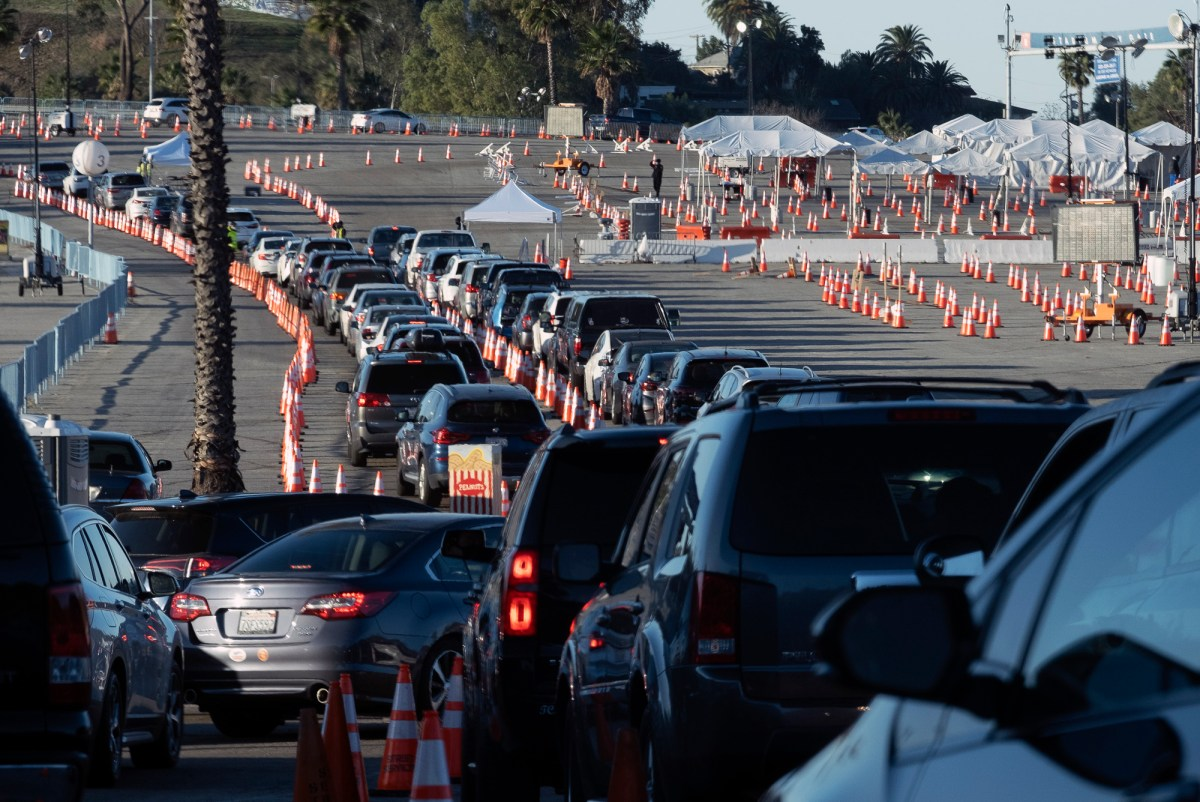 Los Angeles residents wait in line in their cars to receive a covid-19 vaccine at Dodger Stadium, on Jan. 26, 2021, in Los Angeles. California is revamping its vaccine delivery system to give the state more control over who gets the shots following intense criticism of a slow and scattered rollout by counties. Photo by Richard Vogel, AP Photo