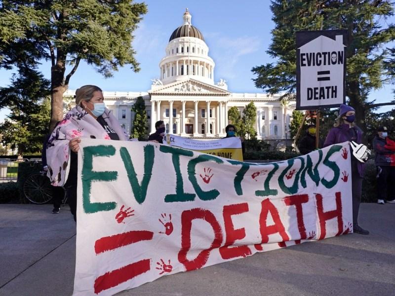 Manifestantes que piden a los legisladores y al gobernador Gavin Newsom que aprueben la condonación de alquileres y una legislación más estricta de protección contra los desalojos se reúnen frente al Capitolio en Sacramento el 25 de enero de 2021. Foto de Rich Pedroncelli, AP Photo