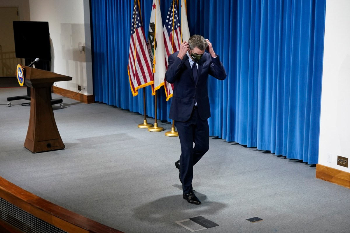 California Gov. Gavin Newsom puts his face mask on after presenting his 2021-2022 state budget proposal at a news conference in Sacramento. AP Photo/Rich Pedroncelli, Pool