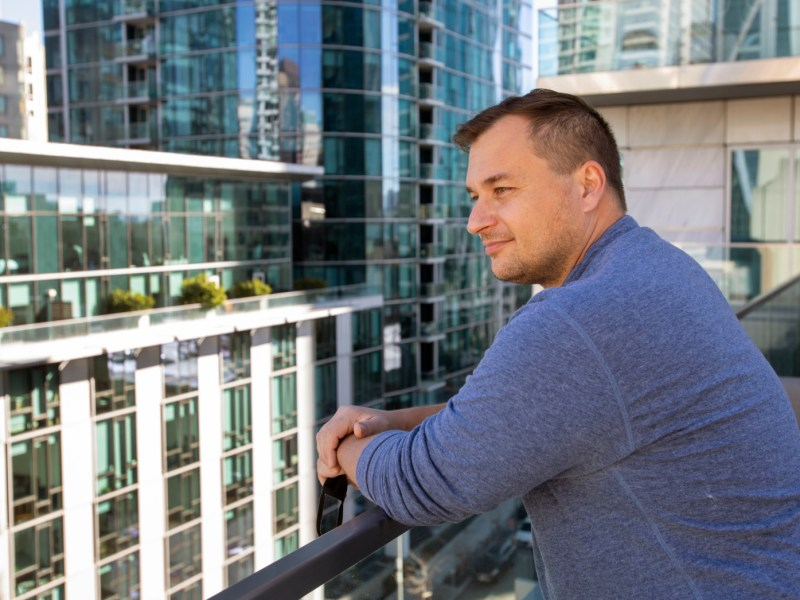 Mykhailo Achey, an IT consultant who moved into better housing in San Francisco. during the pandemic, takes in the balcony view from his downtown highrise, Thursday, Jan. 14, 2021. Photo by Karl Mondon, Bay Area News Group