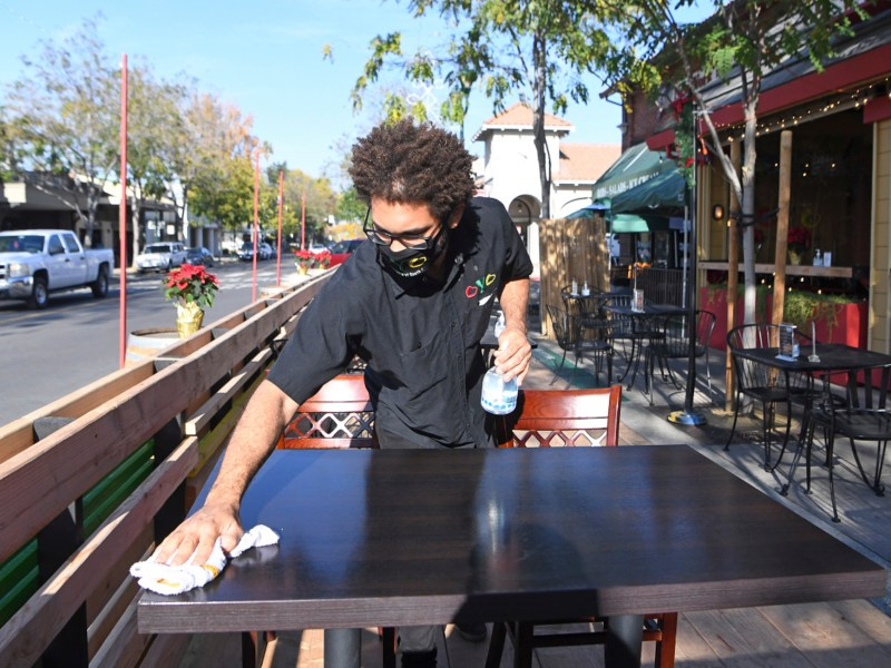 Samuel Dissels cleans a table at Oyo restaurant's newly built outdoor dining area in Pleasanton on Dec. 3, 2020. Public health officials announced Monday that the stay-at-home order has been lifted and counties will return to the color coded tiered system, allowing for businesses to begin reopening. Photo by Doug Duran, Bay Area News Group