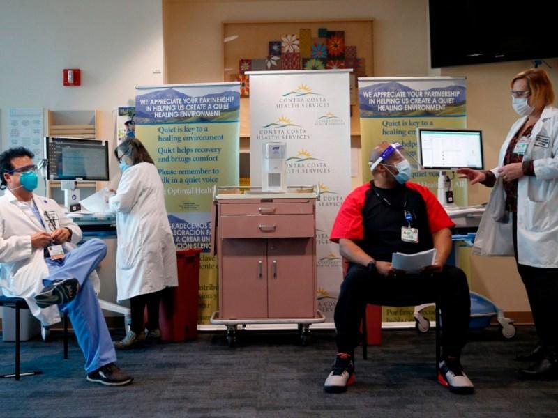 El Dr. Sergio Urcuyo, presidente del Departamento de Medicina Hospitalaria, a la izquierda, se prepara para recibir una vacuna Covid-19 de la enfermera registrada Kathy Ferris, a la izquierda, mientras Holly Longmuir, Gerente del Programa de Control y Prevención de Infecciones, explica el procedimiento a la Enfermera Vocacional Licenciada Henri K .en el Contra Costa Regional Medical Center en Martinez, California, el 15 de diciembre de 2020. Foto de Jane Tyska, Bay Area News Group