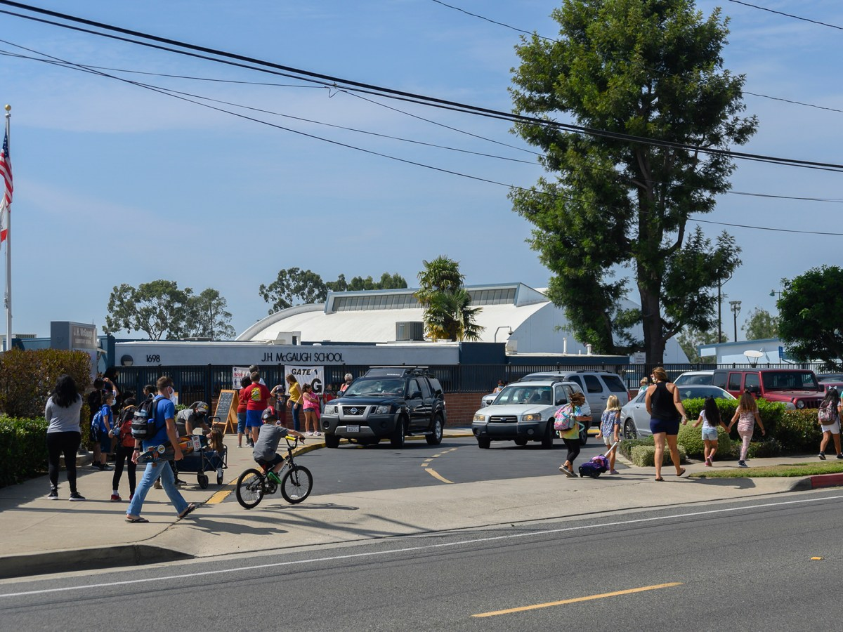 Parents and students mill around the McGaugh Elementary School parking lot during morning and afternoon changeover on Sept. 17, 2020. Photo by Tash Kimmell for CalMatters