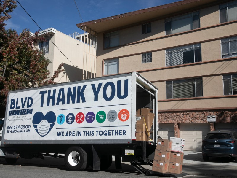 A moving truck with COVID-19 aware messaging outside of an apartment building in Oakland on Nov. 7, 2020. Photo by Anne Wernikoff for CalMatters