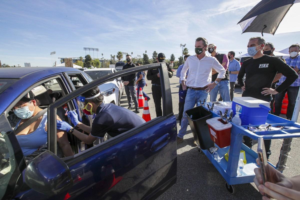 El alcalde de Los Ángeles, Eric Garcetti, a la derecha, y el gobernador Gavin Newsom, en el centro, recorren el sitio de vacunación masiva COVID-19 en el Dodger Stadium, el 15 de enero de 2021, en Los Ángeles. Newsom está bajo el fuego de críticos que cuestionan cómo la planificación del estado aún provocó retrasos en las inyecciones de vacunas. Foto de Irfan Khan, Los Angeles Times vía AP / Pool