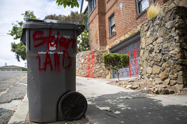 "A spray painted message reads ""Stolen Land"" on a garbage can in front of Oakland Mayor Libby Schaaf's home after police brutality protesters vandalized the city leader's residence onJuly 21, 2020. Photo by Dylan Bouscher/Bay Area News Group"