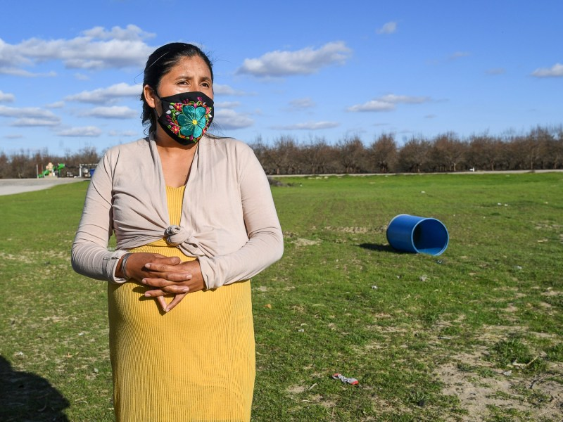 Laura Garcia stands outside her family home in the rural Fresno County community of Raisin City on Feb. 12, 2021. Garcia, a mother of 5 with one on the way, is concerned about how the air quality due to nearby burns is affecting her kids. The orchard in the background replaced a vineyard which was burned away. Photo by Craig Kohlruss, The Fresno Bee