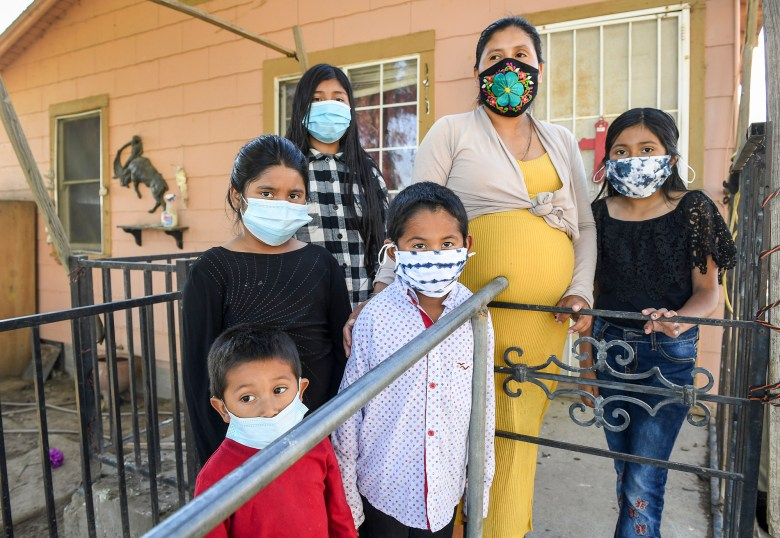 Laura Garcia stands with her children in front of her home in the rural Fresno County community of Raisin City on Feb. 12, 2021. Laura is a mother of 5, with one on the way, and is concerned about how the air quality due to nearby burns is affecting her kids. Photo by Craig Kohlruss, The Fresno Bee