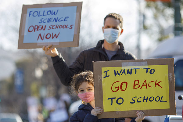 Asaf Bar-Tura and daughter Alma, 7, a first grader, protest near the Albany Unified School District Student Enrollment Center in Albany on February, 10, 2021. Parents and students held the demonstration to call for the reopening of schools. Photo by Anda Chu, Bay Area News Group