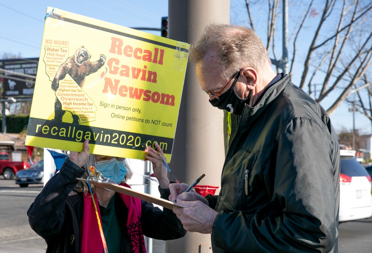 """A volunteer looks on as Sacramento resident Bob Bickers signs the petition to recall Gov. Newsom on Jan. 5, 2021. Bickers, who says he did not vote for Newsom in 2018, would like to see him recalled due to the current 'state of affairs."""" Photo by Anne Wernikoff, CalMatters"""