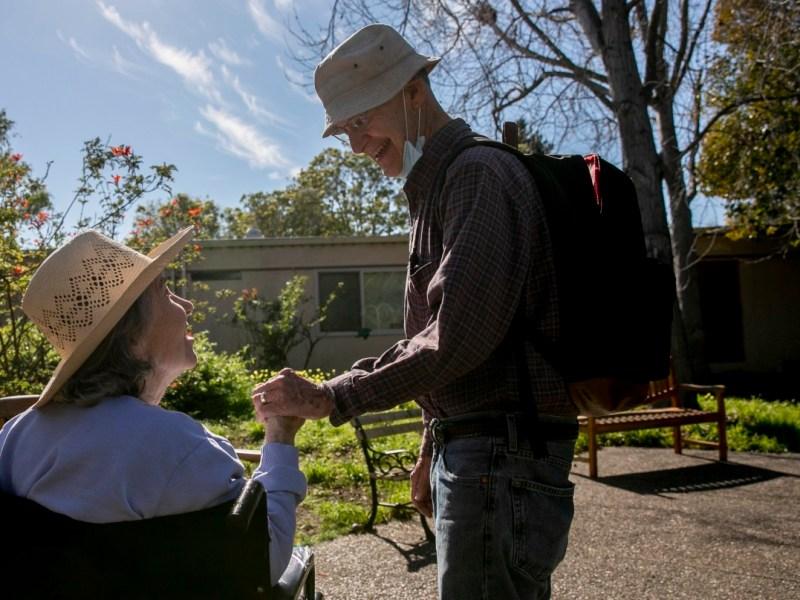 Larry Yabroff y su esposa Mary se saludan durante una visita a Chaparral House, un centro de enfermería especializada donde Mary es residente, en Berkeley el 25 de febrero de 2021. Debido a que ambos están vacunados, el centro les permite tener reuniones que no son socialmente distante. Sin embargo, la mayoría de las instalaciones de California no permiten visitas en persona. Foto de Anne Wernikoff, CalMatters
