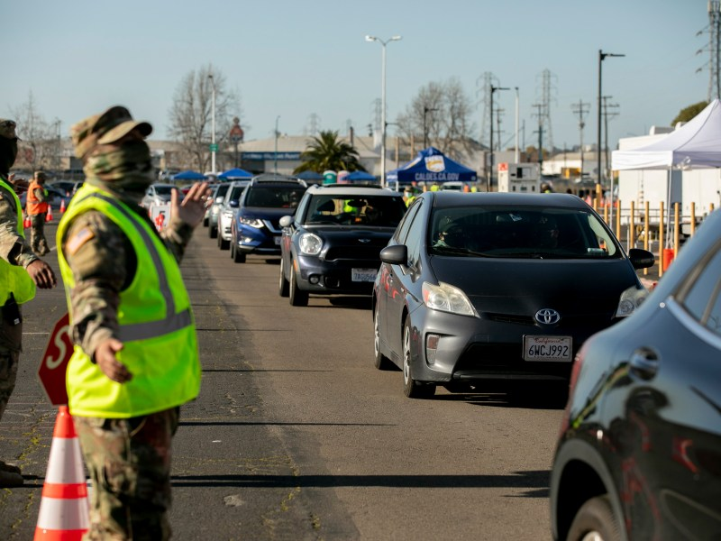 National Guard members direct traffic at a mass drive-thru COVID-19 vaccine distribution clinic at Oakland Coliseum on Feb. 26, 2021. Today, Gov. Newsom announced vaccinations will open up to those 50+ next week and the generally population on April 15. Photo by Anne Wernikoff, CalMatters
