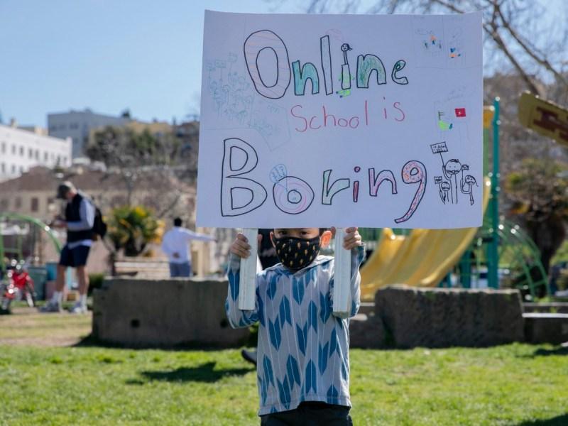 El estudiante de kindergarten de transición Jake Schuman, de 5 años, sostiene un cartel durante una manifestación para reabrir escuelas en Astro Park en Oakland el 28 de febrero de 2021. Foto de Anne Wernikoff, CalMatters