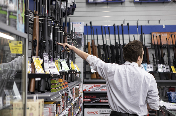 A manager at Big 5 Sporting Goods in El Cerrito points out a long gun from a display on September 9, 2019. Photo by Anne Wernikoff for CalMatters