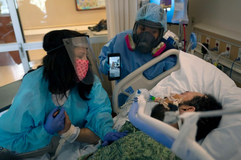 """Patty Trejo, 54, left, looks at her intubated husband, Joseph, in a COVID-19 unit as registered nurse Celina Mande holds a smartphone showing a mariachi band performing for the patient at St. Jude Medical Center, in Fullerton on Feb. 15, 2021. """"He needs to know that I still love him, and he needs to know he's got to fight,"""" said Trejo. Photo by Jae C. Hong, AP Photo"""