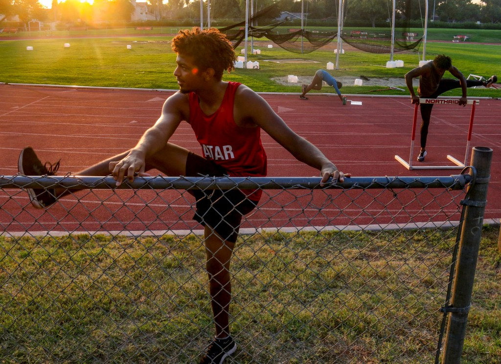 Ahmed Mohamed, left, an international student athlete from Qatar, stretches during a track workout at California State University Northridge alongside teammates Yanla Ndjip-Nyemeck, center, from Belgium and Emmanuel Ihemeje, right, from Italy on Oct. 20, 2020. The team was unable to train with coaches due to COVID-19 restrictions, but a small group of athletes gathered through the pandemic to do socially-distant workouts a couple days a week. Photo by Logan Bik for CalMatters