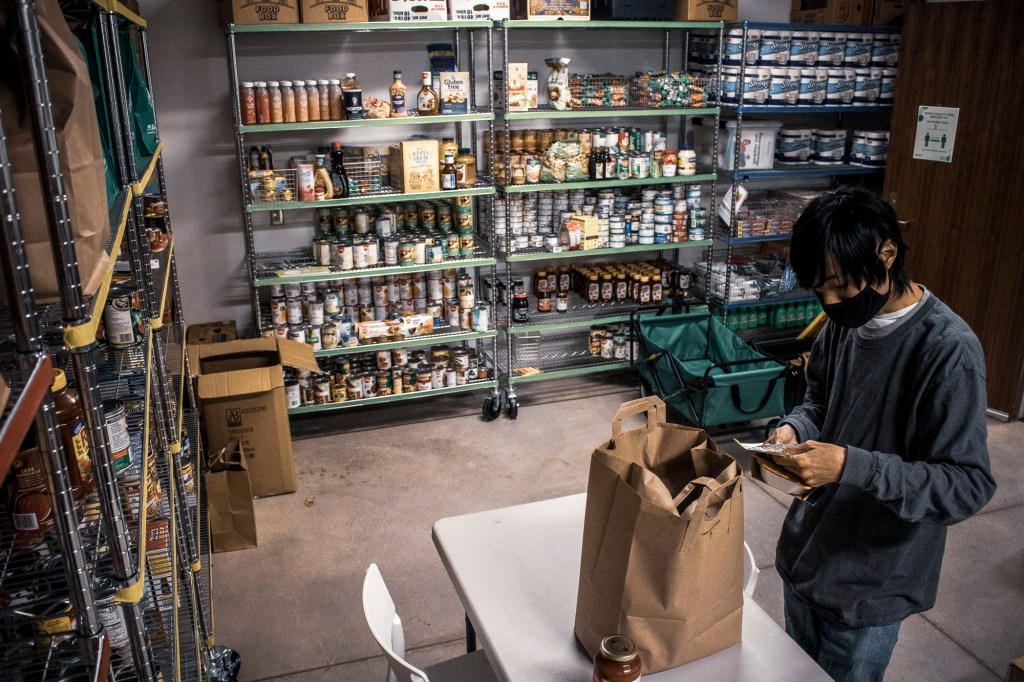 Bao Lee, 27, a graduate student in education and behavioral science, checks a list of food items to collect from the shelves for future distribution at Sacramento State University on Nov. 9, 2020. Lee works with the Associated Students Inc. Food Pantry as a volunteer to help students in need of supplemental groceries. Photo by Rahul Lal for CalMatters