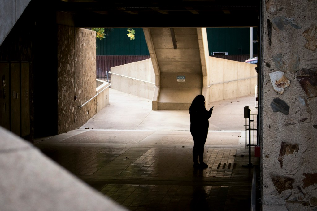 A student checks their phone while waiting for the elevator beneath Eureka Hall at Sacramento State University on Nov. 9, 2020. With few students on campus, the normally a busy throughway remained quiet for much of the day. Photo by Rahul Lal