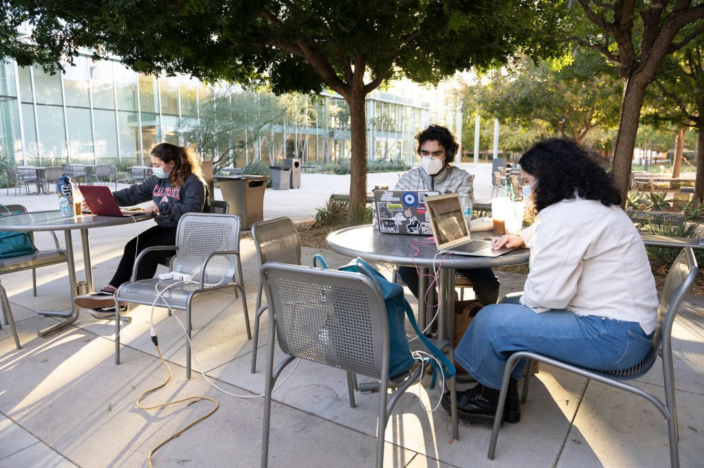 """Psychology major Merna Massoud, left, keeps her distance while studying outside of the performance arts building at Cal State Northridge with her friends Vem and Nairi Nazarian, a chemistry and biology major, respectively, who are siblings on Nov. 10, 2020. """"It's hard to study at home and it's nice to get out in a less populated environment on campus and use the wifi to get some work done."""" Massoud said. Photo by Shae Hammon for CalMatters"""